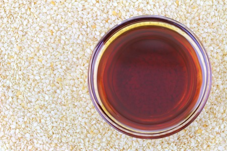 A bowl of cold pressed Sesame oil on white sesame seeds background.