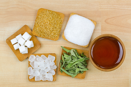 Foto de Sugar cubes, brown sugar crystals, granulated white sugar, rock sugar, stevia, honey, Different types of sweetness, top view on wooden background - Imagen libre de derechos