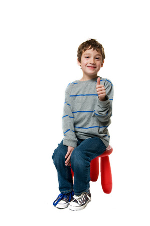 cute little boy sitting on a red stool on a white background
