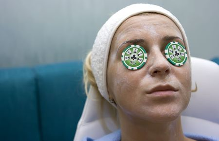 Poker chips lying on eyes like cucumbers in spa salon