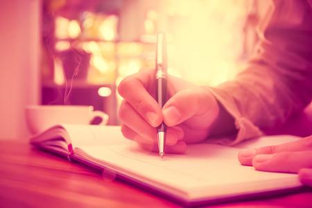 Photo pour Man hand holding a pen writing on the notebook. - image libre de droit