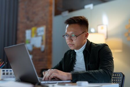 Foto de education, deadline and people concept - close up of creative man in glasses working at night office and thinking happy asian freelancer korean man laptop - Imagen libre de derechos