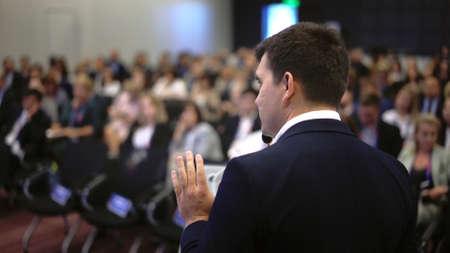 Speaker business meet talk audience from stage in microphone. Presenter economic forum speak public. Educational speech business man. Speaker talking group people at symposium. Presentation men.