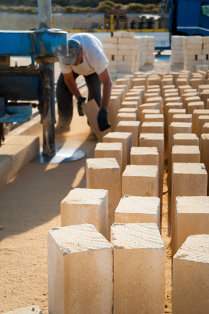 Just cut tufa blocks while a worker is using a sawing machine to cut the stone horizontally