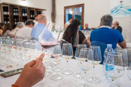 Hand of a taster holding a glass of wine during a degustation event