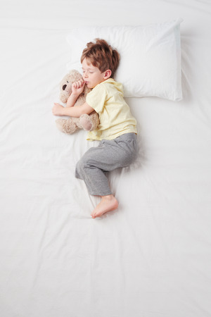 Top view photo of little cute boy sleeping on white bed with teddy bear.