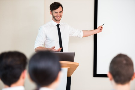 Photo of handsome young businessman making presentation with whiteboard on seminar or meeting to business people