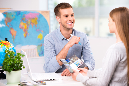 Photo of male travel agent and young woman. Young man smiling and offering vacation options for female tourist. Travel agency office interior with big world map