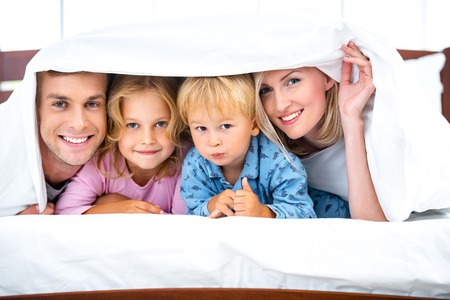 Photo pour Photo of loving family of four lying on white bed in morning. Family hiding under blanket - image libre de droit