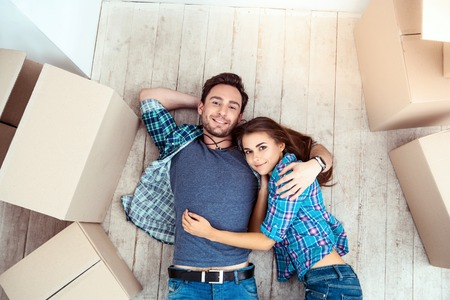 Happy young couple lying on floor near moving boxes. Young family moving to new home. Woman and man smiling and looking at camera