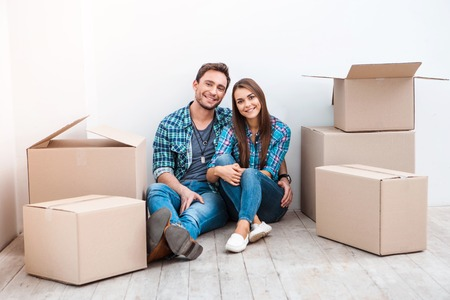 Happy young couple sitting on floor near moving boxes. Young family moving to new home. Woman and man smiling and looking at camera