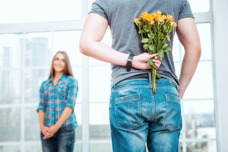 Romantic photo of happy young couple. Young man making surprise for his girlfriend. Man holding bouquet of yellow flowers behind his back