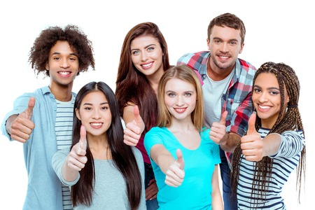 Photo pour Studio shot of nice young multicultural friends. Beautiful people showing thumbs up, looking at camera and cheerfully smiling. Isolated background - image libre de droit