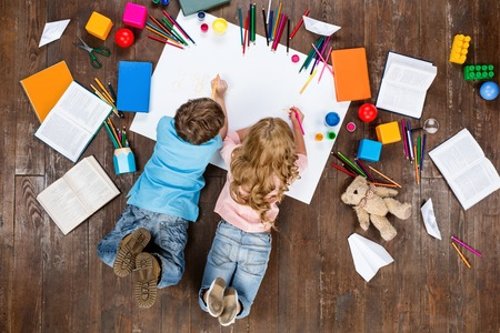 Happy children. Top view creative photo of little boy and girl on vintage brown wooden floor. Children lying near books and toys, and painting