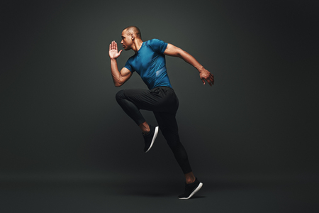 Foto de Deserve Victory. Sportsman jumping over dark background, he is ready to run - Imagen libre de derechos