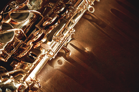 Photo pour Close up and detailed view of a shiny keys of a golden saxophone lying on leather sofa. Musical instruments. - image libre de droit