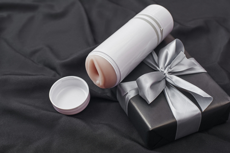 Sex toy gift for man you love! Close-up photo of male masturbator and gift box arranged on a black silk fabric