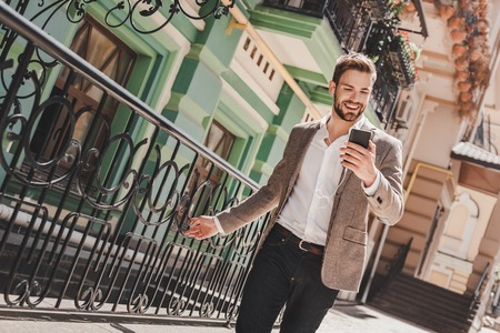 Great news! Smiling brown-haired man standing outdoors and using his smartphone. He holds his phone and touches fence beside him