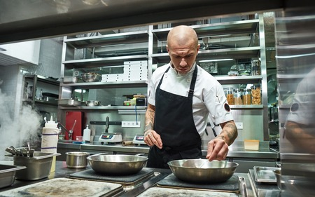 Confidence in everything. Serious male chef with several tattoos on his arms frying ingredients for his dish in a restaurant kitchen