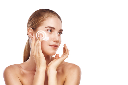 Foto de Perfect skin. Beautiful young woman applying cosmetic cream on her face while standing against white background. Beauty products - Imagen libre de derechos