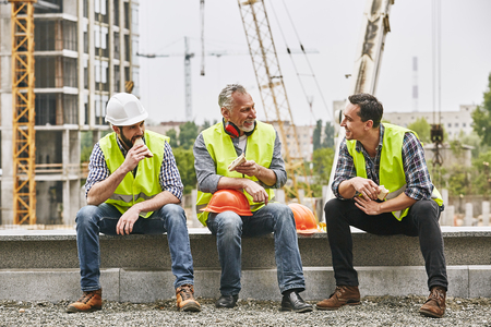 Photo pour Time for a break. Group of builders in working uniform are eating sandwiches and talking while sitting on stone surface against construction site. Building concept. Lunch concept - image libre de droit