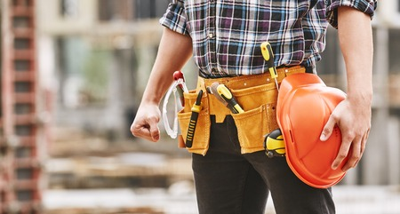 Photo pour Safe work. Cropped photo of male professional builder with construction tools holding a safety red helmet while standing outdoor of construction site - image libre de droit