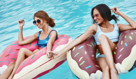 Photo pour Pools of fun. Girls relaxing with inflatable rings in the shape of donuts - image libre de droit