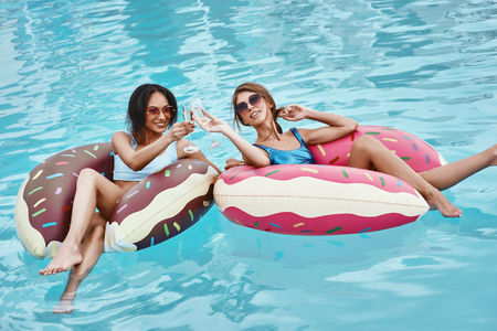 Photo pour Memories of the Holidays. Girls relaxing with inflatable rings in the shape of donuts - image libre de droit