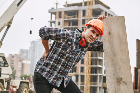 Photo pour Hard work. Construction worker in protective helmet feeling back pain while working at construction site. Building construction. Pain concept - image libre de droit