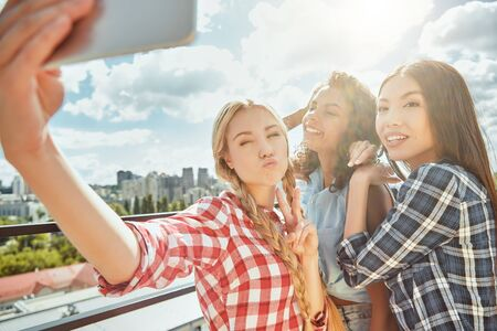 Photo pour Group of cheerful and young women are making selfie and smiling at camera while having barbecue on the roof. - image libre de droit