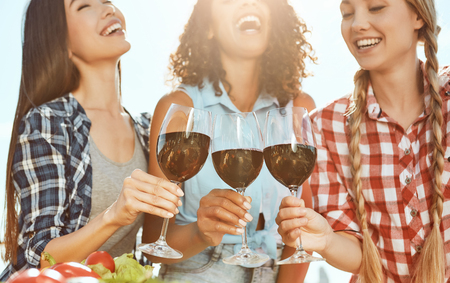 Photo pour Cheers! Three young and happy women holding glasses with wine and laughing while standing on the roof. Barbecue concept. Summer concept. Friendship - image libre de droit