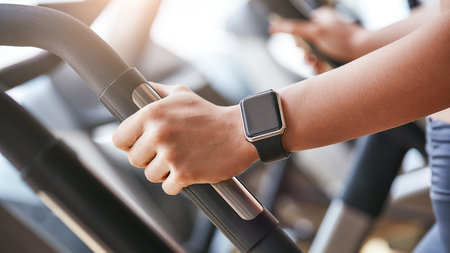 Photo pour Smart technologies. Close-up photo of smart watch on woman hand holding the handle of cardio machine in gym. Fitness and sport concept. - image libre de droit
