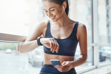 Photo pour Making training easier. Young and cheerful woman in sportwear looking at her sport bracelet and using smartphone while standing in front of window at gym - image libre de droit