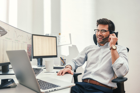 Photo pour Good news. Happy young bearded trader in headset talking with client and smiling while sitting in his modern office. Business concept. Trade concept. Communication concept - image libre de droit