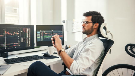 Trading online. Back view of young bearded trader in formal wear and eyeglasses using his smartphone while sitting in his office. Forex market. Trade concept. Investment concept