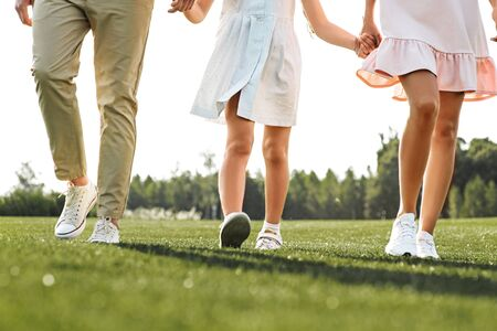 Photo pour Family day. Cropped photo of happy young family of three holding hands and walking outdoors. Concept of a happy family. Picnic. Weekend - image libre de droit