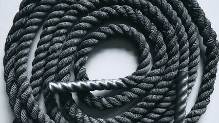 Foto de Close up of black battle rope on a gray backgound. Sport and fitness equipment. Functional training - Imagen libre de derechos