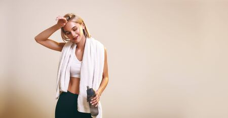 Photo pour It was great workout Cute and young sporty woman in sports clothing with towel on shoulders keeping eyes closed and smiling while standing in studio - image libre de droit