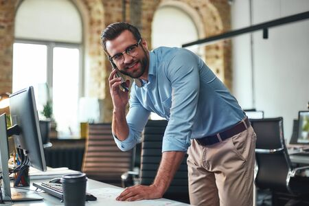Photo pour Business talk. Portrait of young and cheerful bearded man in eyeglasses talking on smart phone and using computer while standing in the modern office - image libre de droit