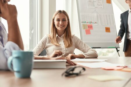 Photo pour Great presentation. Young and cheerful woman looking at camera with smile while her boss standing near whiteboard and explaining something on the background - image libre de droit