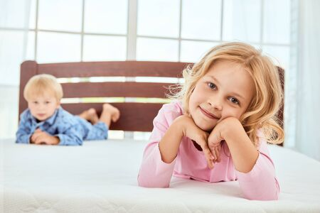 Photo pour Being at home. Cute little sister and her brother in pajamas lying on a big white mattress and looking at camera with smile - image libre de droit