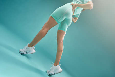 Photo for Female slender legs in sports shorts and sneakers - Royalty Free Image