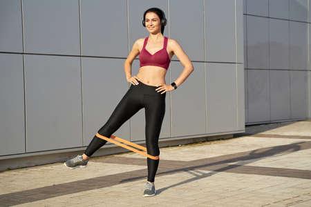 Foto für Smiling sportswoman in wireless headphones doing exercises - Lizenzfreies Bild