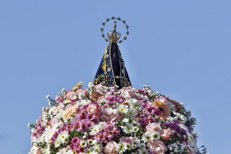 Photo for Statue of the image of Our Lady of Aparecida, mother of God in the Catholic religion, patroness of Brazil, decorated with flowers - Royalty Free Image