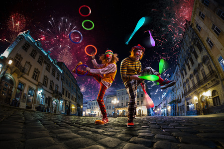 Photo pour Night street circus performance whit two clowns, juggler. Festival city background. fireworks and Celebration atmosphere. - image libre de droit