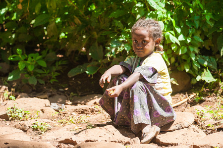 OMO, ETHIOPIA - SEPTEMBER 20, 2011: Unidentified Ethiopian beautiful little girls sits on the ground and takes a rest. People in Ethiopia suffer of poverty due to the unstable situation