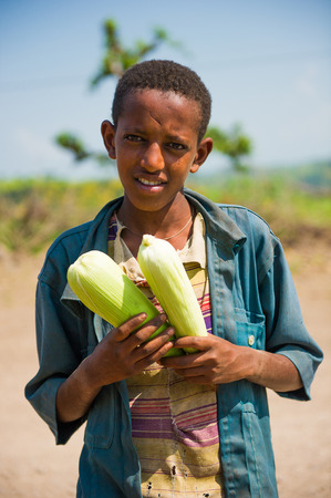 AKSUM, ETHIOPIA - SEPTEMBER 22, 2011: Unidentified Ethiopian boy sells maiz in the desert. People in Ethiopia suffer of poverty due to the unstable situation