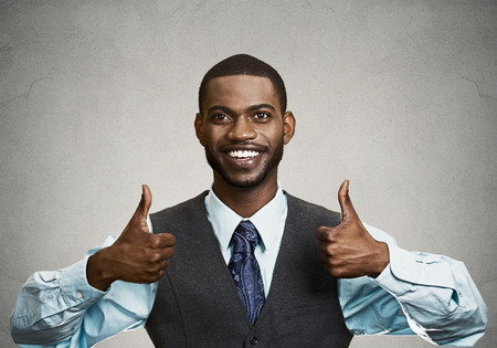 Closeup portrait handsome young smiling business man, corporate employee giving thumbs up sign at camera isolated black grey background. Positive human emotions, facial expression, feelings. Symbols