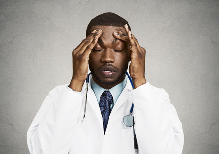Closeup portrait sad health care professional with headache, stressed, holding head with hands. Nurse, doctor with migraine overworked, overstressed isolated black background. Negative human emotions