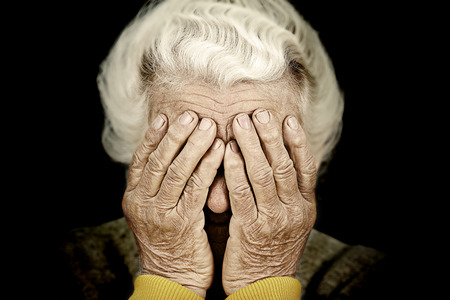 Foto de Closeup portrait sad depressed, stressed, thoughtful, senior, old woman, gloomy, worried, covering her face, isolated black background. Human face expressions, emotion, feelings, reaction, attitude - Imagen libre de derechos